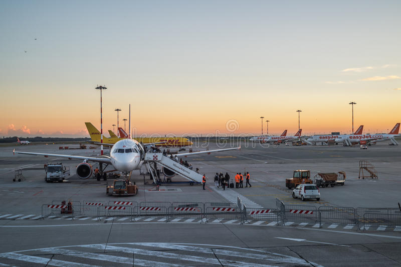People board a commercial airplane at Milan Malpensa airport at sunset in Milan stock image