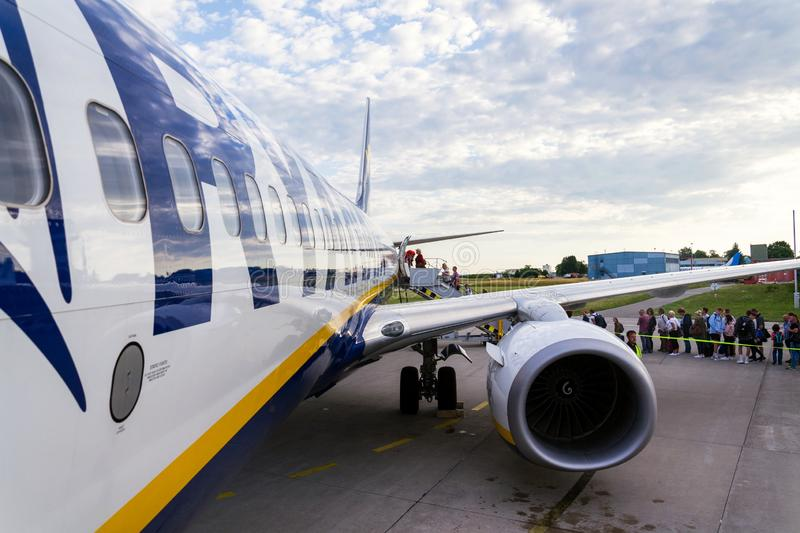 People boarding Ryanair Irish low-cost airline plane Boeing 737 with cloudy sky background. MEMMINGEN, GERMANY - JULY 6 2019: People boarding Ryanair Irish low stock photography