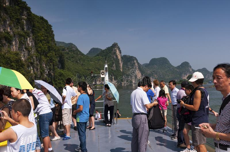 People in a boat cruising in the Li River and looking at the the tall limestone mountains near Yangshuo in China royalty free stock photo