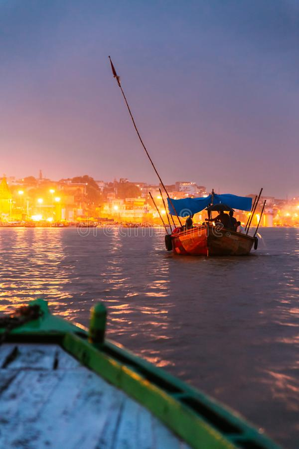 People on the boat floating on the river are going to pray at Varanasi Ganga Aarti at holy Dasaswamedh Ghat. People on the boat floating on the river are going royalty free stock image