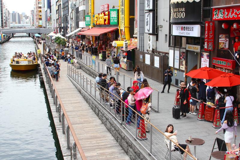 People boat restaurants boulevard Dotonbori river, Osaka. Bridge, boat and people sitting on outdoor cafe restaurant street terrace at boulevard along Dotonbori stock image