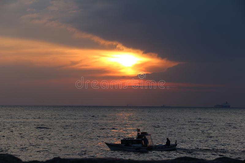 People in a boat on a sea at sunset. Two fisherman in a boat on a sea at sunset. From Istanbul, Turkey stock photography