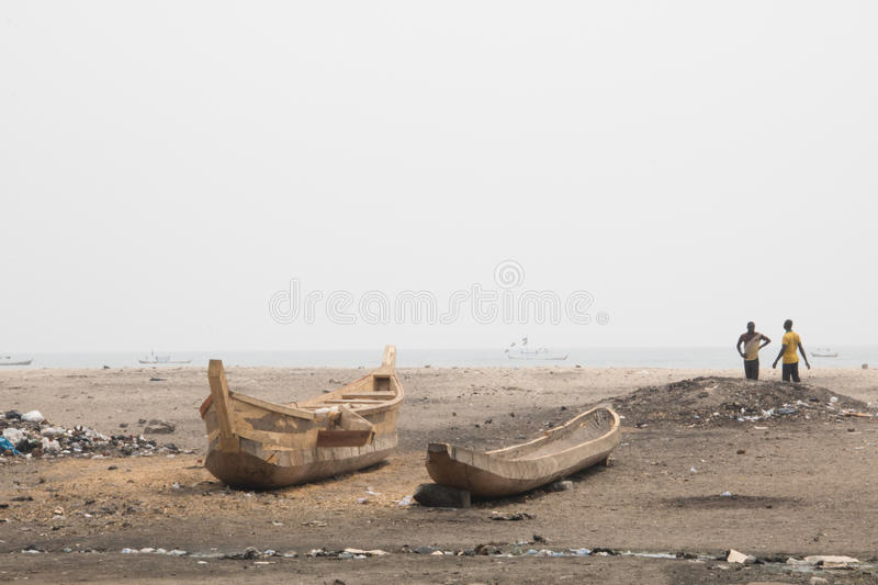 People and boats on a beach in Jamestown, Accra, Ghana. ACCRA, GHANA - JANUARY 2016: People and fishing boats on a beach in Jamestown, Accra, Ghana at the Gulf stock images