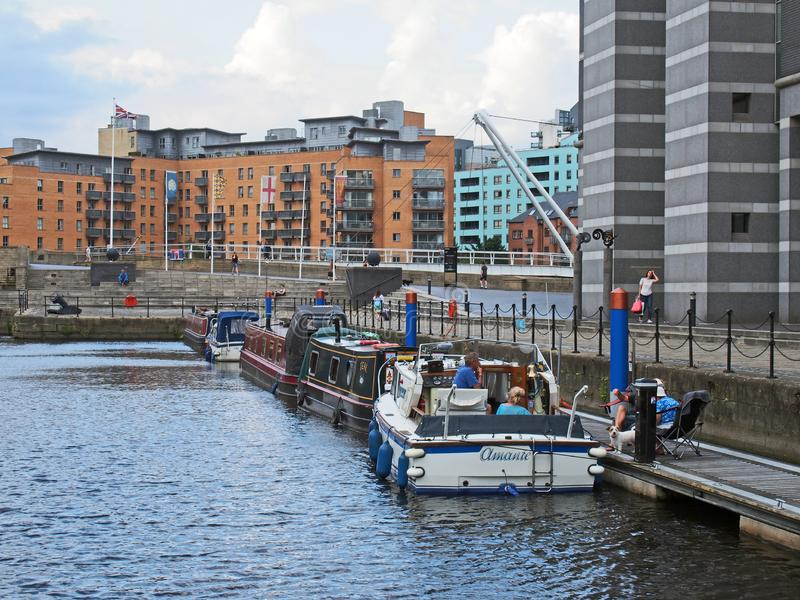 People on boats moored in leeds dock with surrounding apartment buildings. Leeds, west yorkshire, united kingdom - 16 july 2019: people on boats moored in leeds stock photo