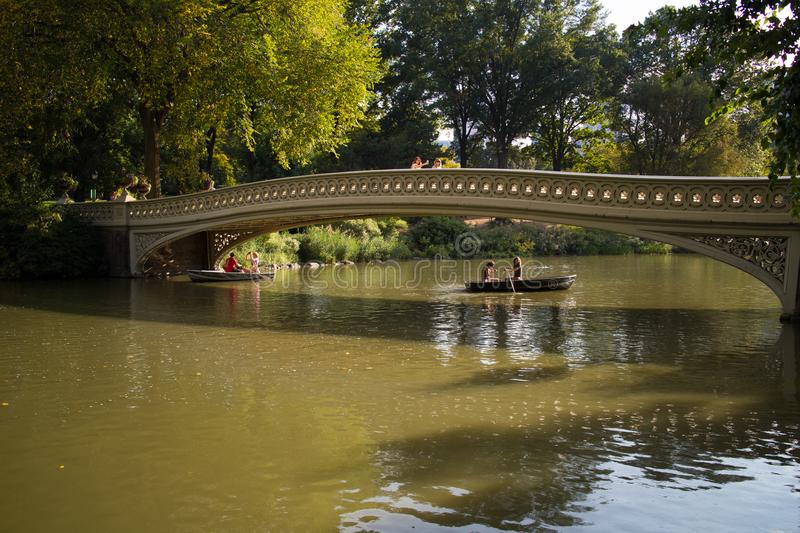 People in Boats Under Bow Bridge in Central Park, Manhattan, New York City royalty free stock photos