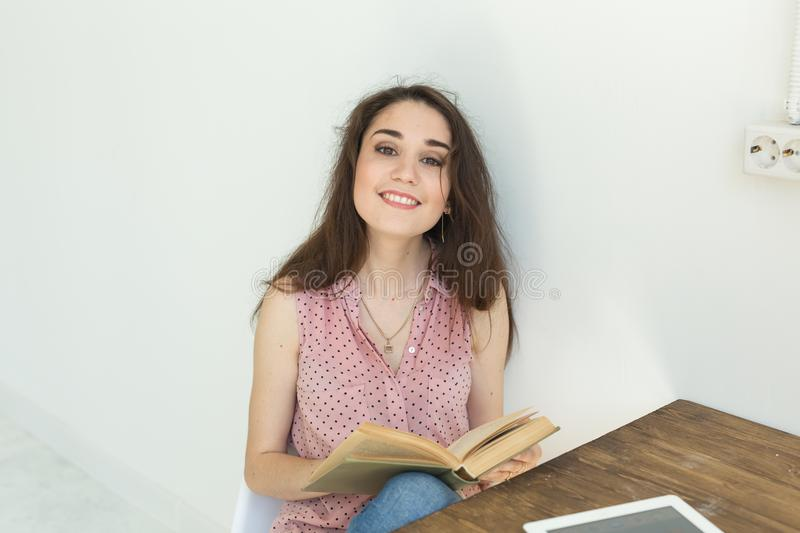 People, books and education concept - portrait of happy female student sitting with a book stock images