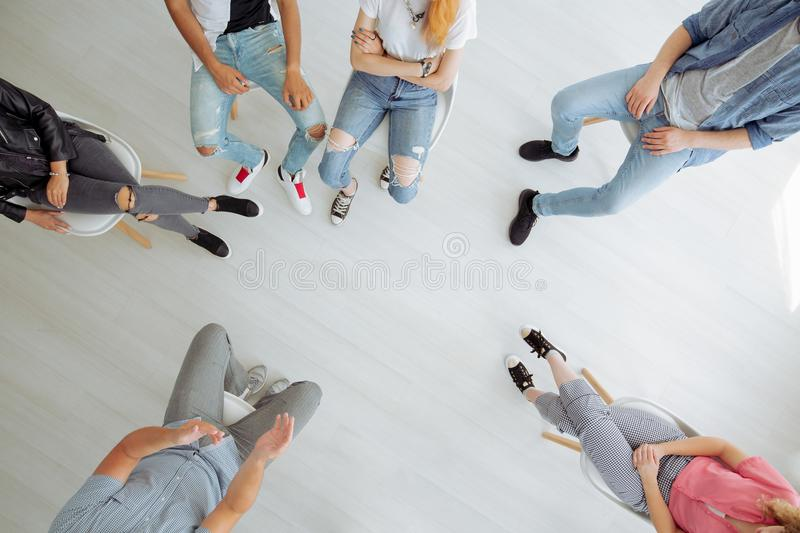 People brainstorming in the circle. High angle of young rebellious people sitting in a circle during brainstorming stock photos
