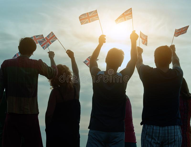 People with british flags. Silhouette of patriotic family against sky background stock images