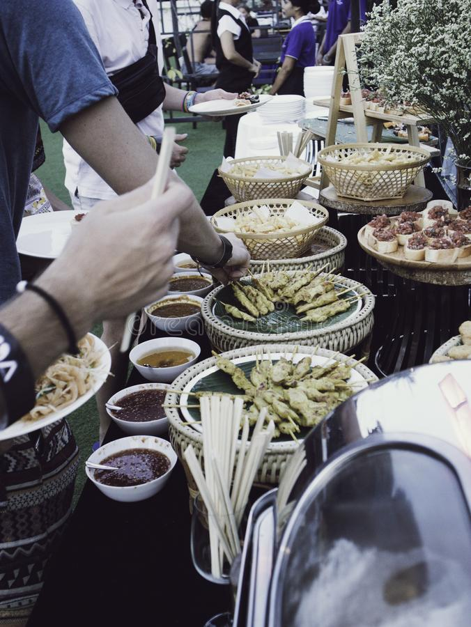 People at a Buffet table with a variety of dishes. A meal where guests serve themselves from a variety of dishes set out on a table or sideboard. And restaurants royalty free stock photo