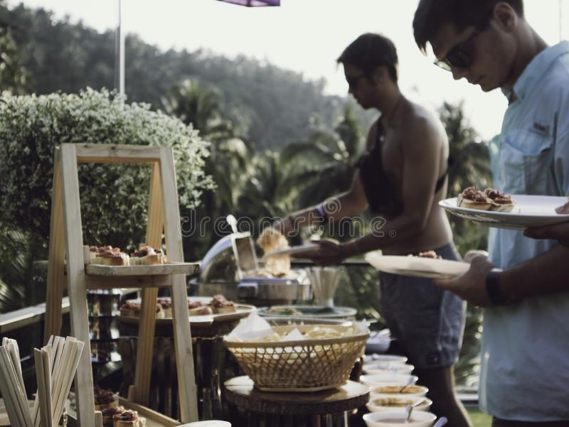 People at a Buffet table with a variety of dishes stock image