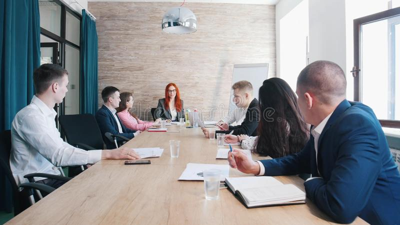 People at the business conference in the office. A ginger woman chief holding a hand on the papers stock photos