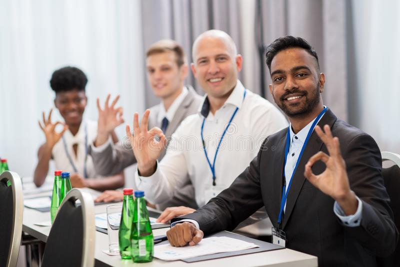 People at business conference showing ok hand sign. Business, gesture and education concept - group of happy people at international conference showing ok hand royalty free stock photos