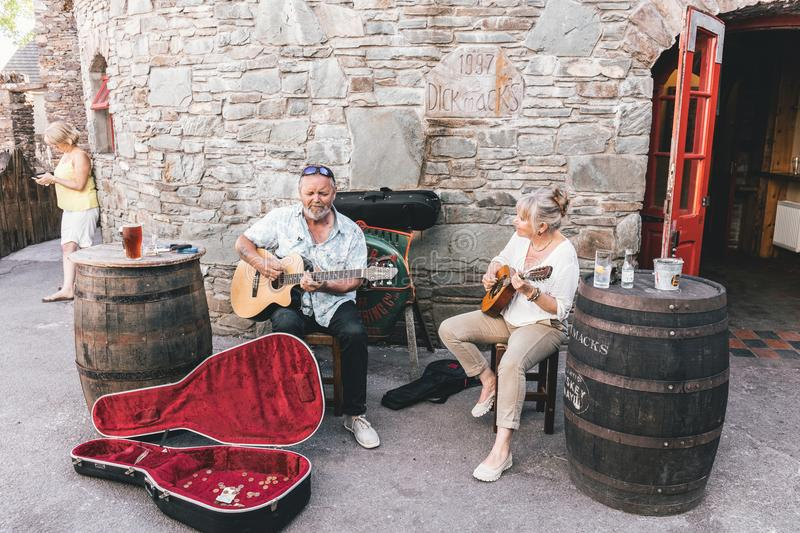People busking near the pubs in the small port town on the southwest of Ireland Dingle Peninsula. June 4th, 2018, Dingle, Ireland - small port town on the royalty free stock photos