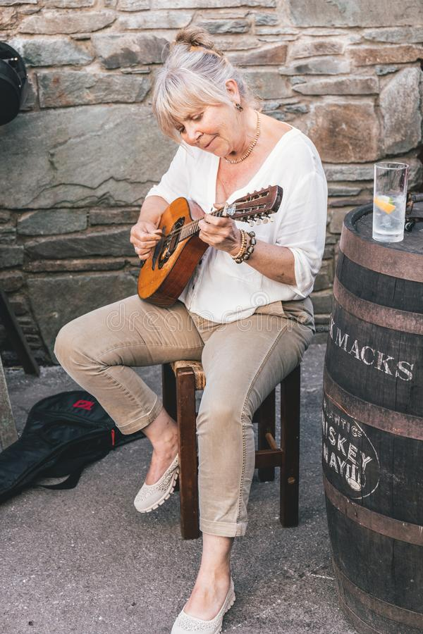 People busking near the pubs in the small port town on the southwest of Ireland Dingle Peninsula. June 4th, 2018, Dingle, Ireland - small port town on the stock photos