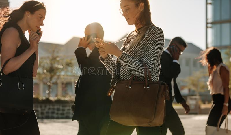 People busy using mobile phone while walking on street to office stock photography