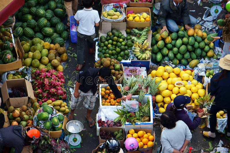 People buy and sell fruit at market.DA LAT, VIET NAM- FEBRUARY 8, 2013 stock photography