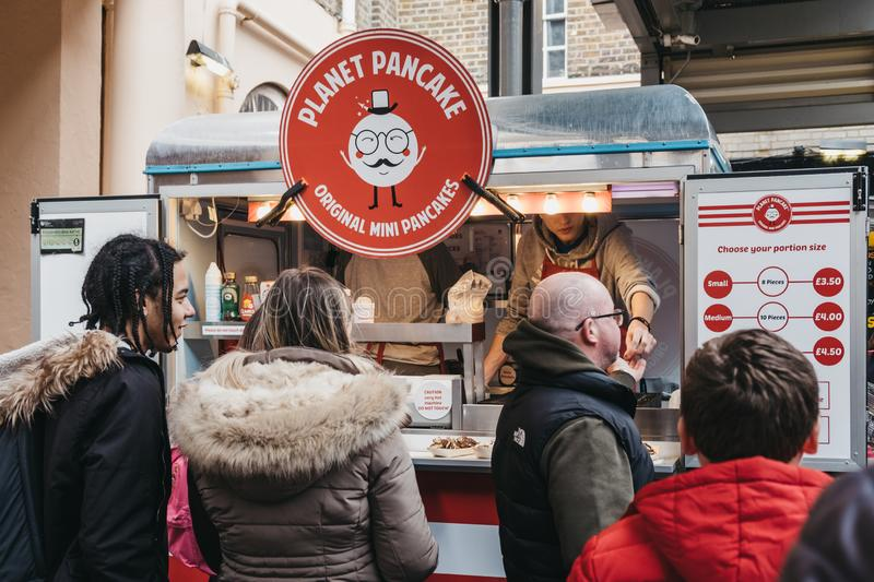 People buying mini pancakes from a Planet Pancake stand at Greenwich Market, London,UK stock photography