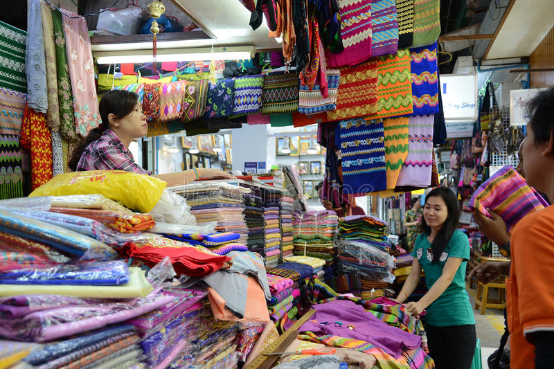 People buying traditional burmese clothes. Yangon, Myanmar - April 26, 2016 : People buying traditional burmese clothes in a clothes shop in Bogyoke market stock image