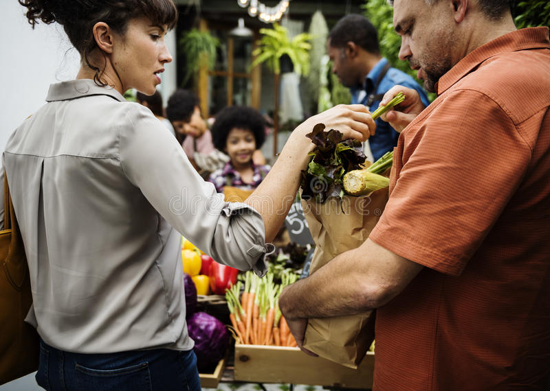 People Buying Vegetable From Shop at Market Concept. People Buying Vegetable From Shop at Market royalty free stock photography