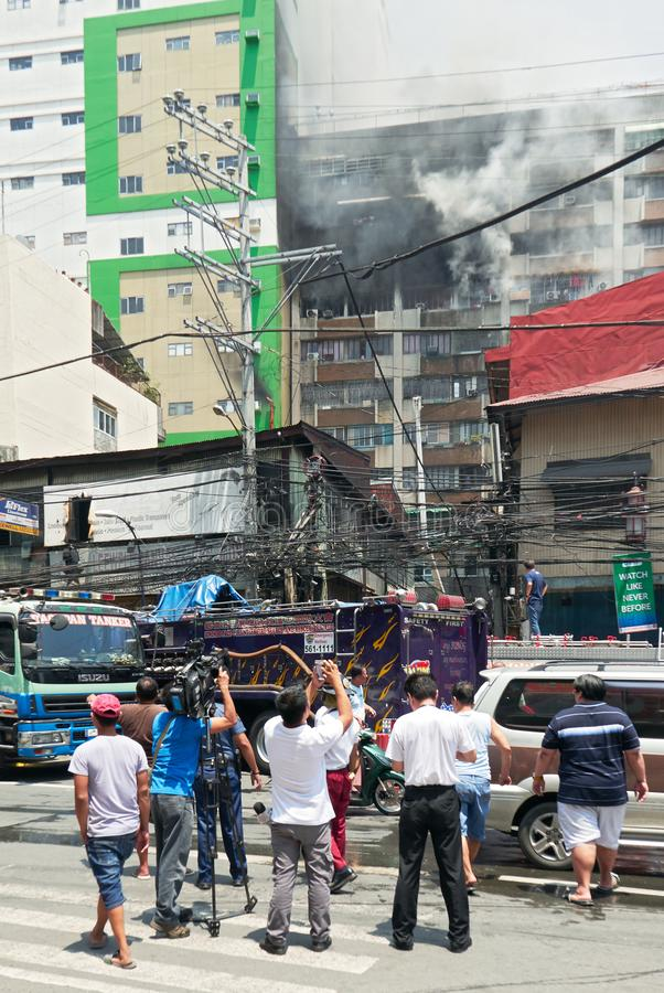 People and camera man watching a fire in Binondo, Manila. Manila, Philippines: Deadly fire in an apartment building in Binondo with group of men and camera man stock image