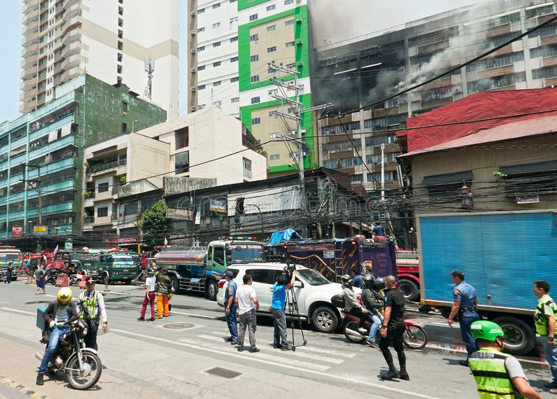 People and camera man watching a fire in Binondo, Manila. Manila, Philippines - September 7, 2017: Deadly fire in an apartment building in Binondo with group of royalty free stock photos