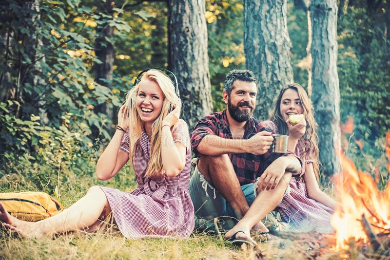 People camping at fire in forest in vintage style. Friends relax at bonfire flame with sparks. Women and bearded man at royalty free stock image