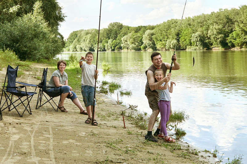 People camping and fishing, family active in nature, child caught fish on bait, river and forest, summer season royalty free stock photography