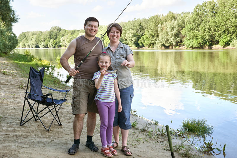 People camping and fishing, family active in nature, child caught fish on bait, river and forest, summer season royalty free stock images