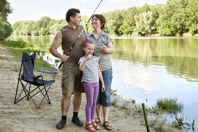 People camping and fishing, family active in nature, fish caught on bait, river and forest, summer season stock images