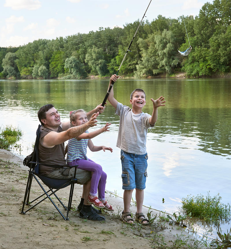 People camping and fishing, family active in nature, fish caught on bait, river and forest, summer season royalty free stock photos