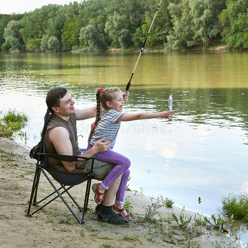 People camping and fishing, family leisure in nature, fish caught on bait, river and forest, summer season stock photos