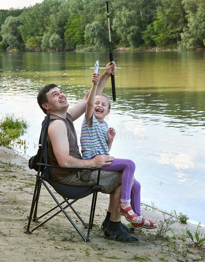 People camping and fishing, family leisure in nature, fish caught on bait, river and forest, summer season stock image