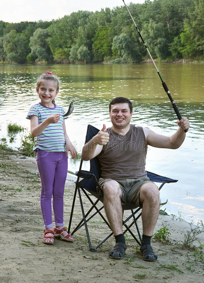 People camping and fishing, family leisure in nature, fish caught on bait, river and forest, summer season royalty free stock photo