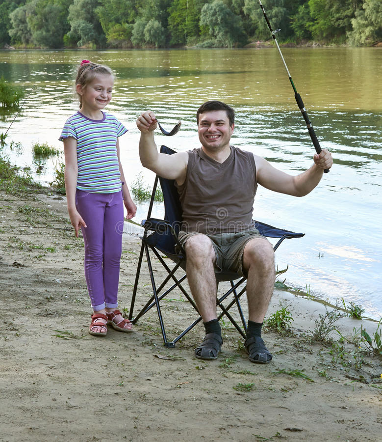 People camping and fishing, family leisure in nature, fish caught on bait, river and forest, summer season royalty free stock photos