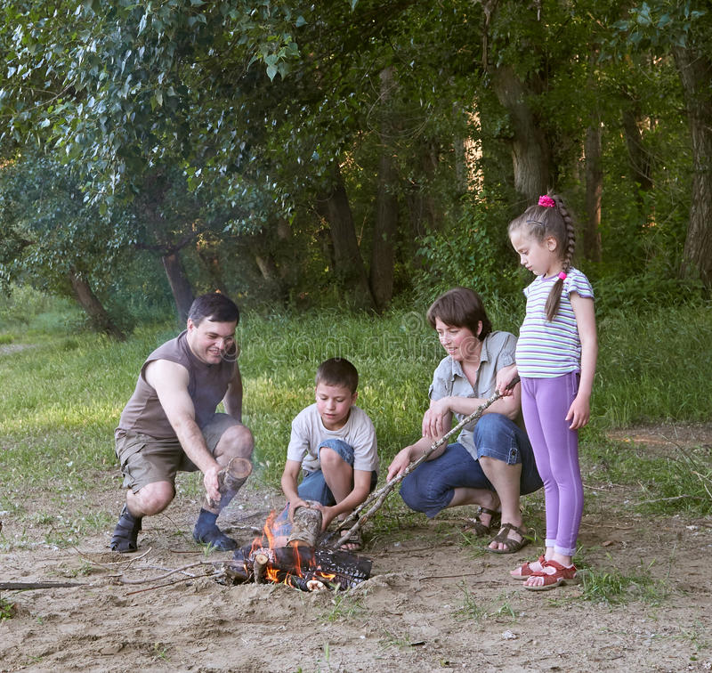People camping in forest, family active in nature, kindle fire, summer season royalty free stock image