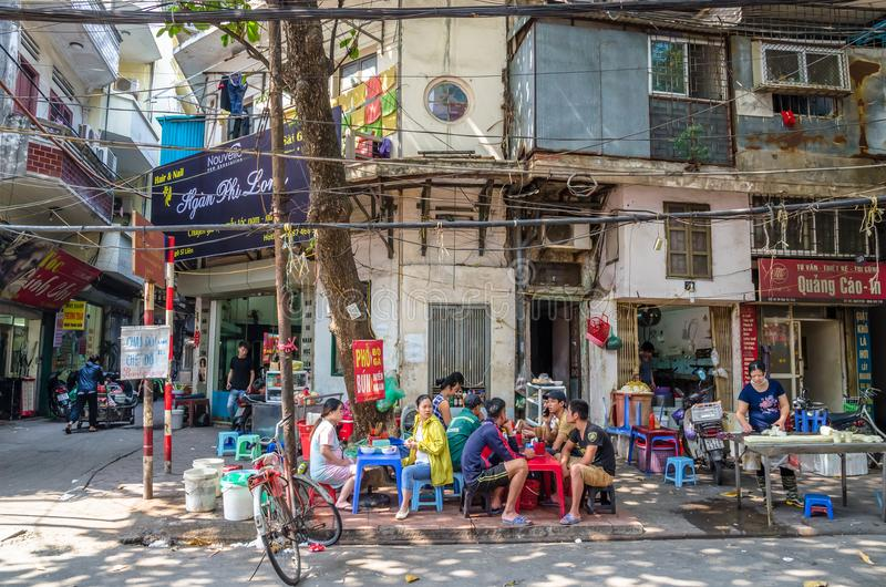 People can seen having their food beside the street in the morning at Hanoi, Vietnam. royalty free stock photos