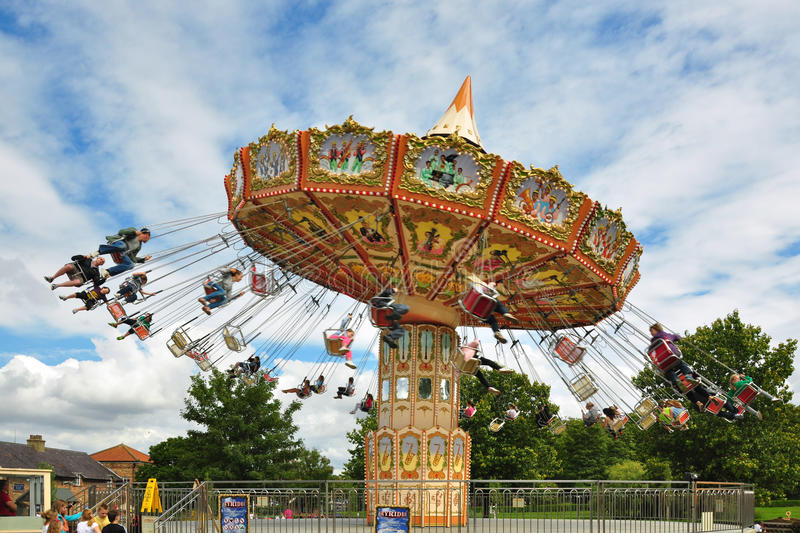 People on carousel under blue sky with clouds