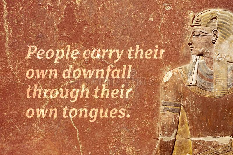 Own downfall EP2. People carry their own downfall through their own tongues - ancient Egyptian proverb printed on red grunge wall royalty free stock image