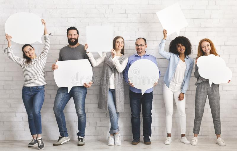 People carryng speech bubble icons at studio. People carrying speech bubble icons with free space, standing at white brick wall, ready for your text stock images