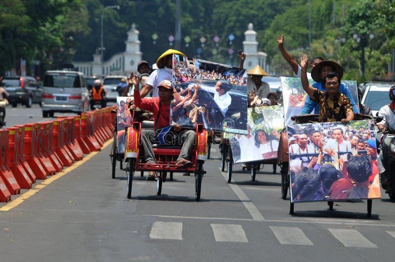 People CelebrateThe Inaguration of Indonesian New President. SURAKARTA, INDONESIA - October 20 : Residents carrying a big poster of Indonesian new president royalty free stock photos