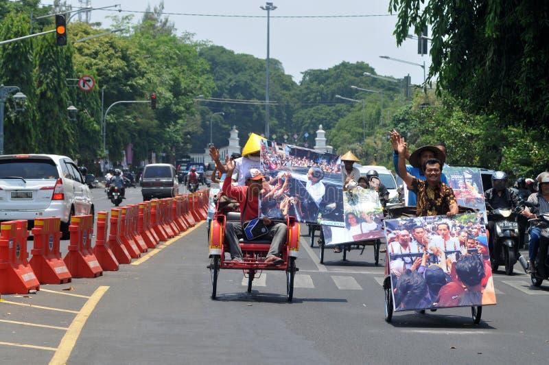 People CelebrateThe Inaguration of Indonesian New President. SURAKARTA, INDONESIA - October 20 : Residents carrying a big poster of Indonesian new president stock photo