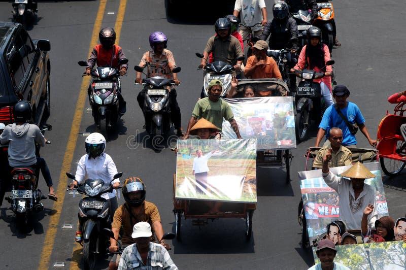People CelebrateThe Inaguration of Indonesian New President. SURAKARTA, INDONESIA - October 20 : Residents carrying a big poster of Indonesian new president royalty free stock photo