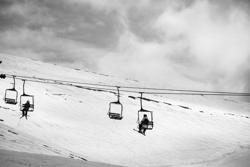 People on chair lift. People highing up the chair lift in the top of the ski piste royalty free stock image
