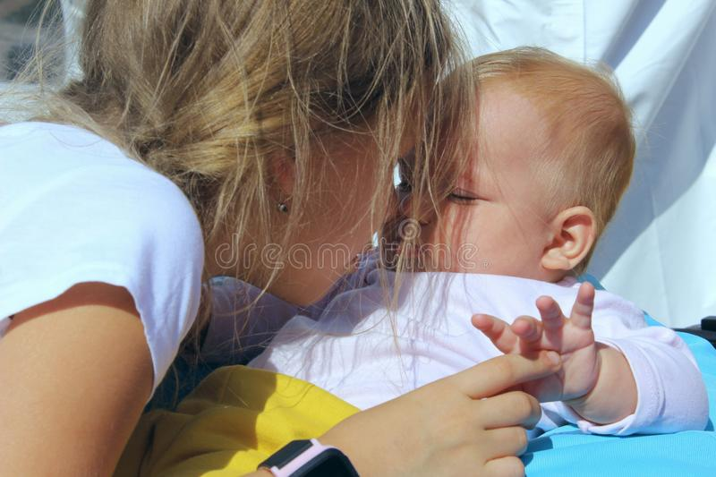 People, childhood, family concept. Cropped shot of a cute baby girl over blue sky background. Sisters hugs. stock photography