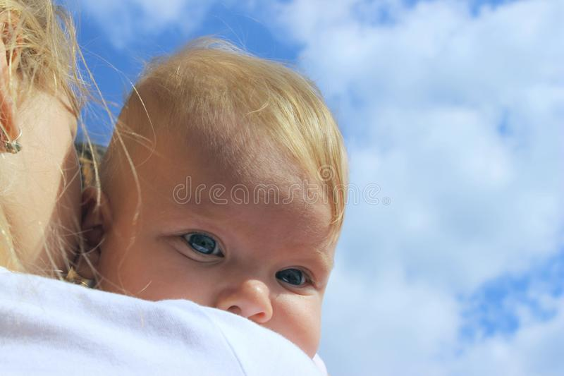 People, childhood, family concept. Cropped shot of a cute baby girl over blue sky background. Sisters hugs. People, childhood, family concept. Cropped shot of a royalty free stock images