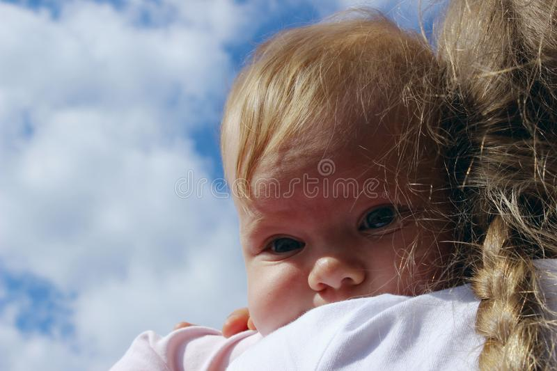 People, childhood, family concept. Cropped shot of a cute baby girl over blue sky background. Sisters hugs. royalty free stock photography