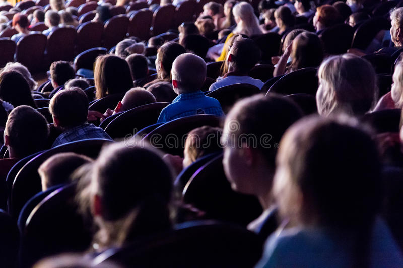 People, children, adults, parents in the theater. People in the auditorium looking at the stage. Shooting from the back stock photos