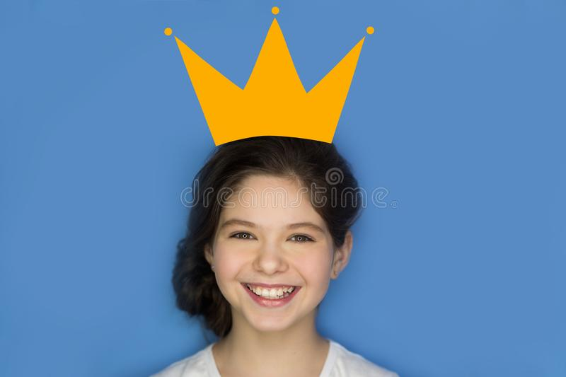People, children, concept of imagination and fairy tales - smiling girl with crown doodle over head, on blue royalty free stock photos