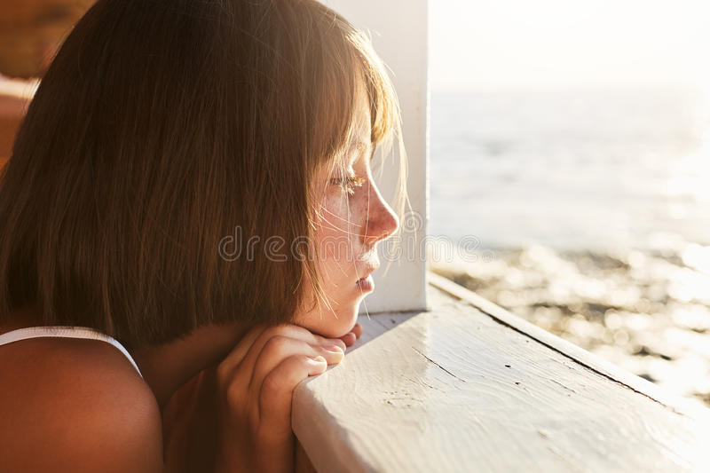 People, children, relaxation, calmness concept. Adorable kid leaning at wooden deck, looking ar sea landscapes with dreamy express. Ion, thinking about something royalty free stock images