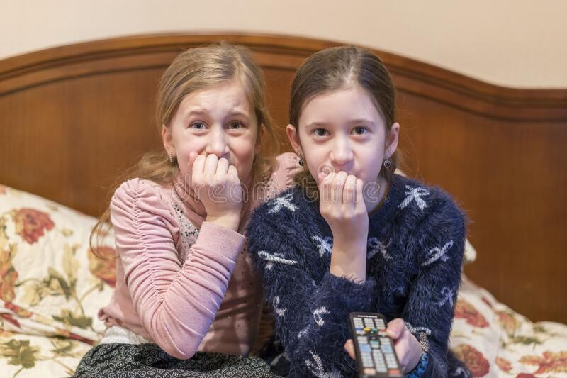 People, children, television, friends and friendship concept - two scared little girls watching horror on tv at home. toned stock images